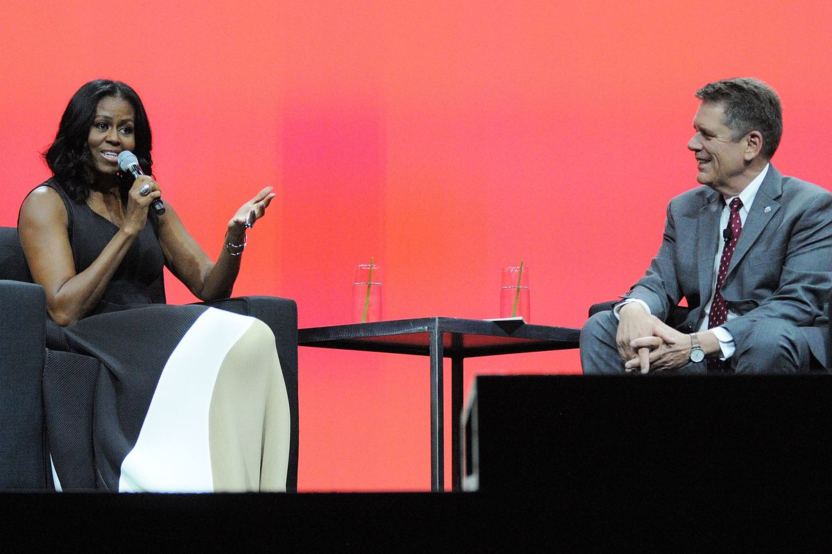 Photo of a man and woman sitting on a stage with a red backdrop.