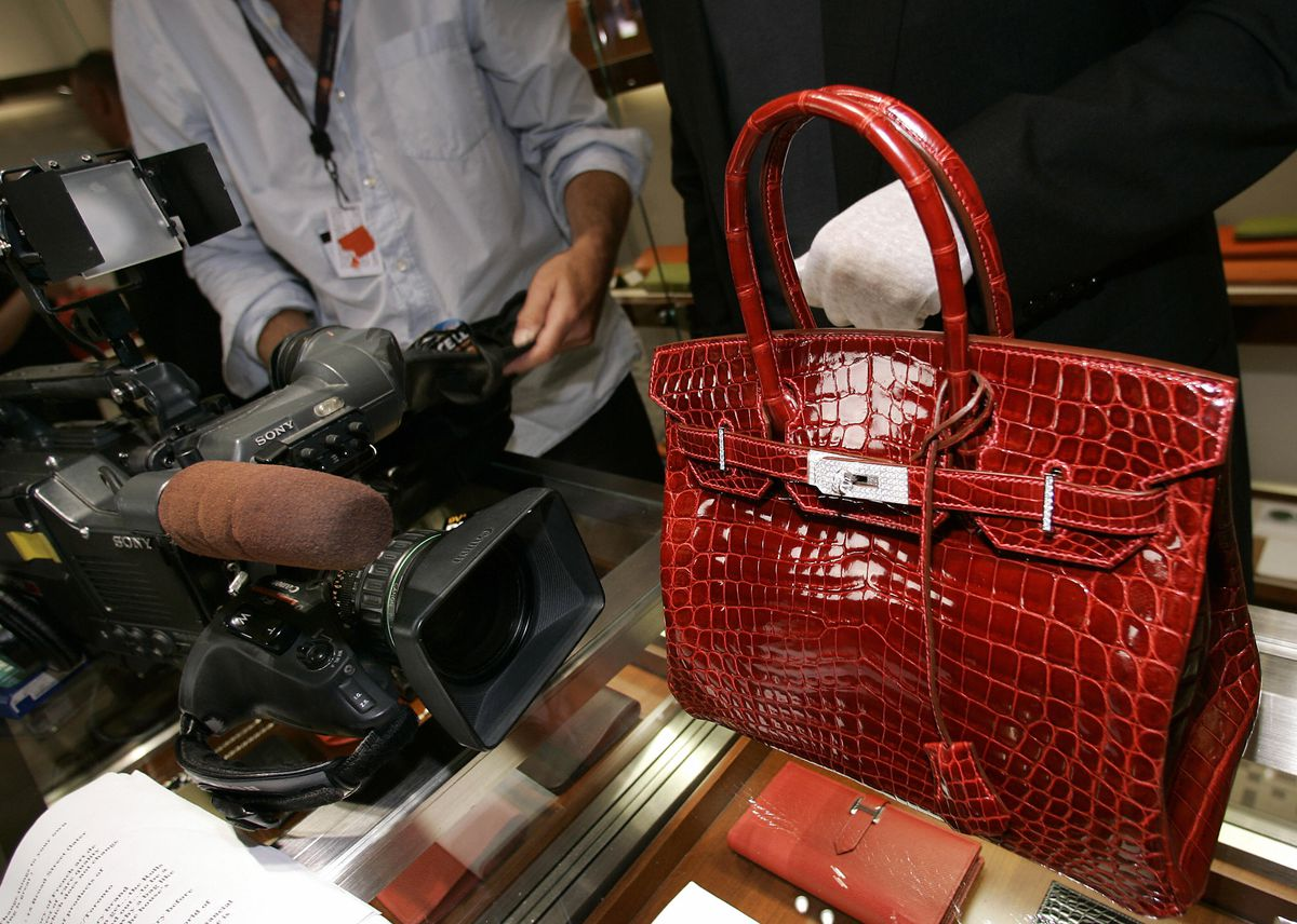 A glossy red crocodile bag sits on a glass counter.
