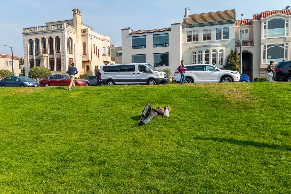 An apparently homeless man sleeping on a lawn in the Marina.