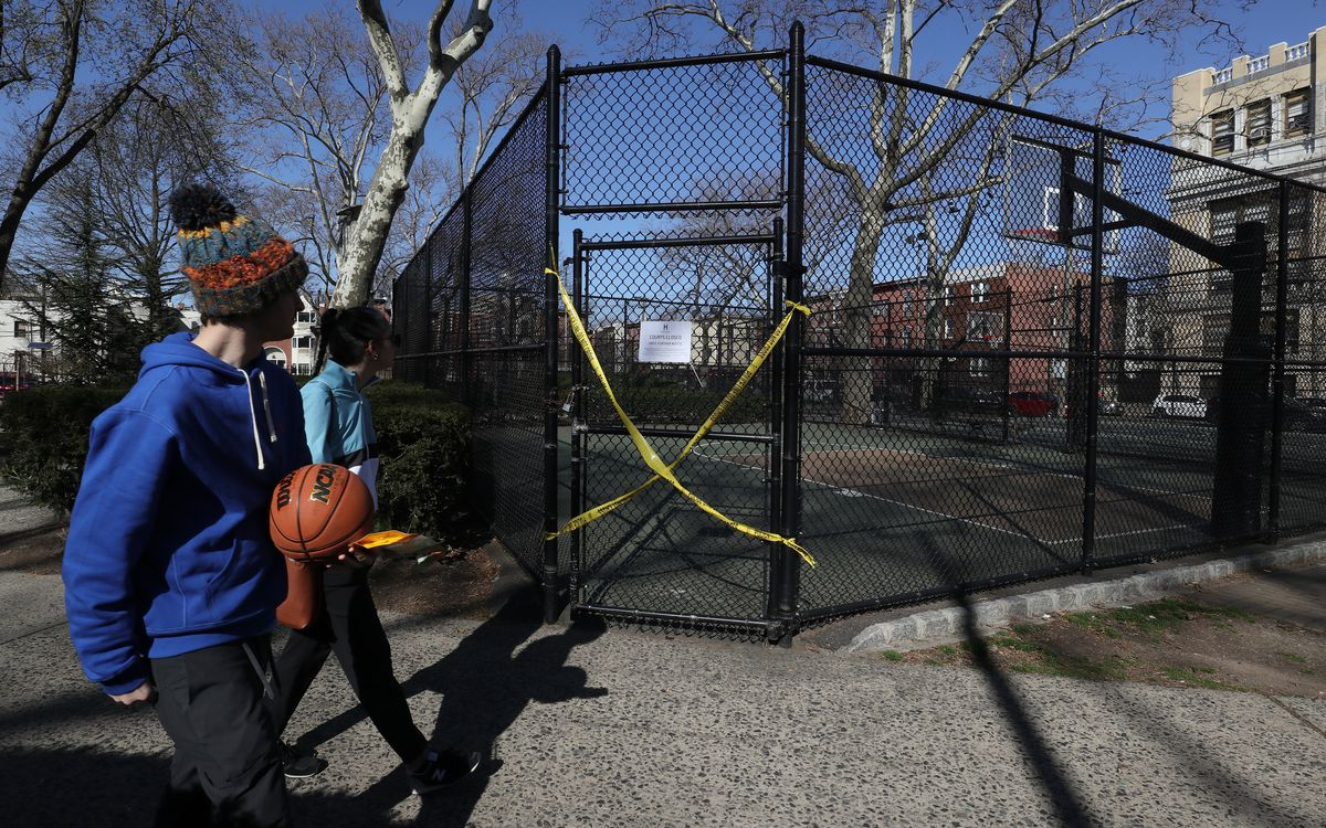 People walk past a basketball court after the closure of playgrounds on March 15, 2020 in Hoboken, New Jersey. The municipal government in Hoboken has taken strong measures against the community spread of the coronavirus (COVID-19) by closing, schools, playgrounds, limiting restaurants to take-out only and instituting a curfew beginning on March 16.