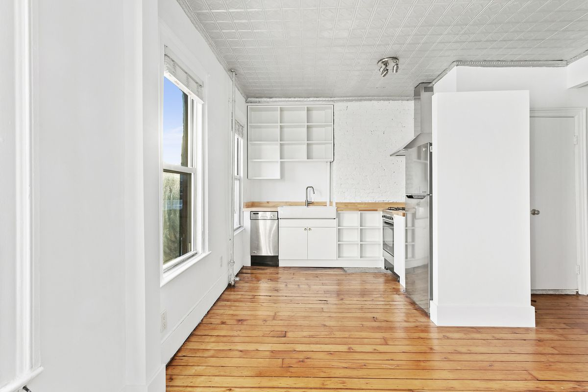 A kitchen with white cabinetry and two windows.