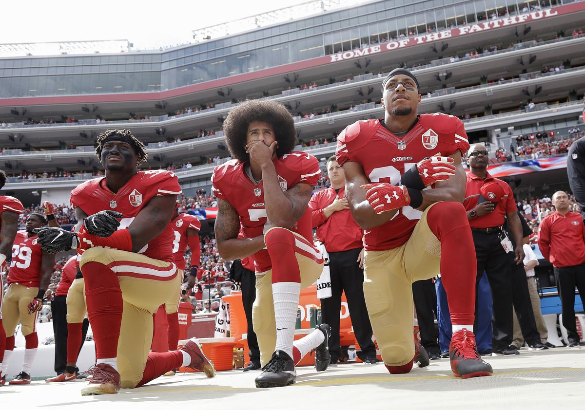 San Francisco 49ers outside linebacker Eli Harold (left), then-quarterback Colin Kaepernick and safety Eric Reid kneel during the national anthem before an NFL football game against the Dallas Cowboys in October 2016.   Marcio Jose Sanchez/AP photo