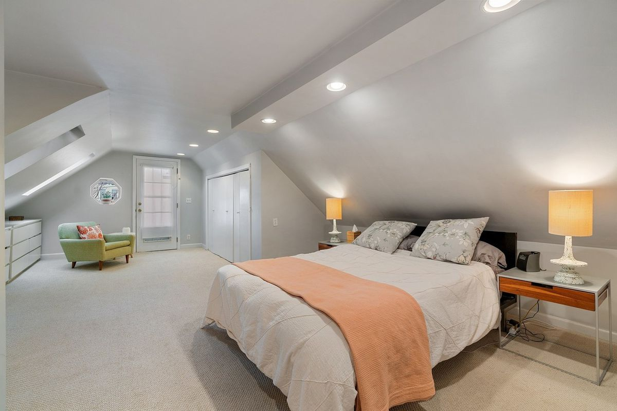 A master bedroom with carpet, a bed, and two night stands with lamps. There are dressers and a chair in the background.
