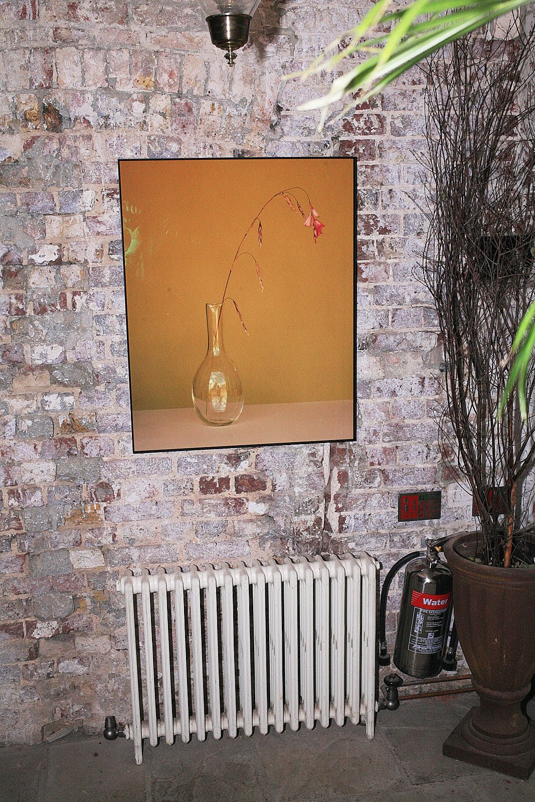 Gold art, a radiator, and an exposed brick wall in Sessions Arts Club dining room