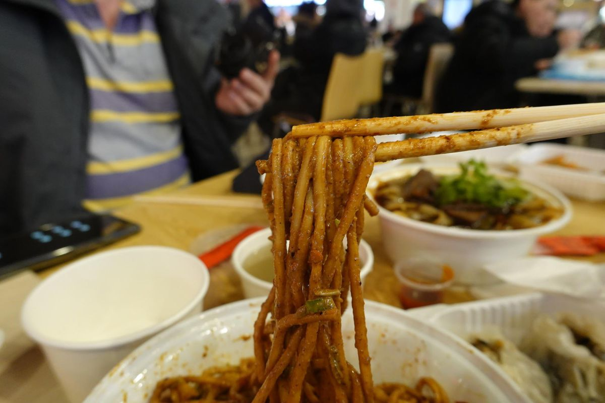 A pair of chopsticks can be seen picking up a brownish-colored noodles