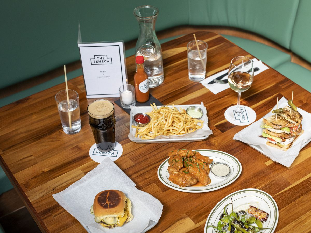 A wooden dining table with burgers, fries, wings, and beers on it.