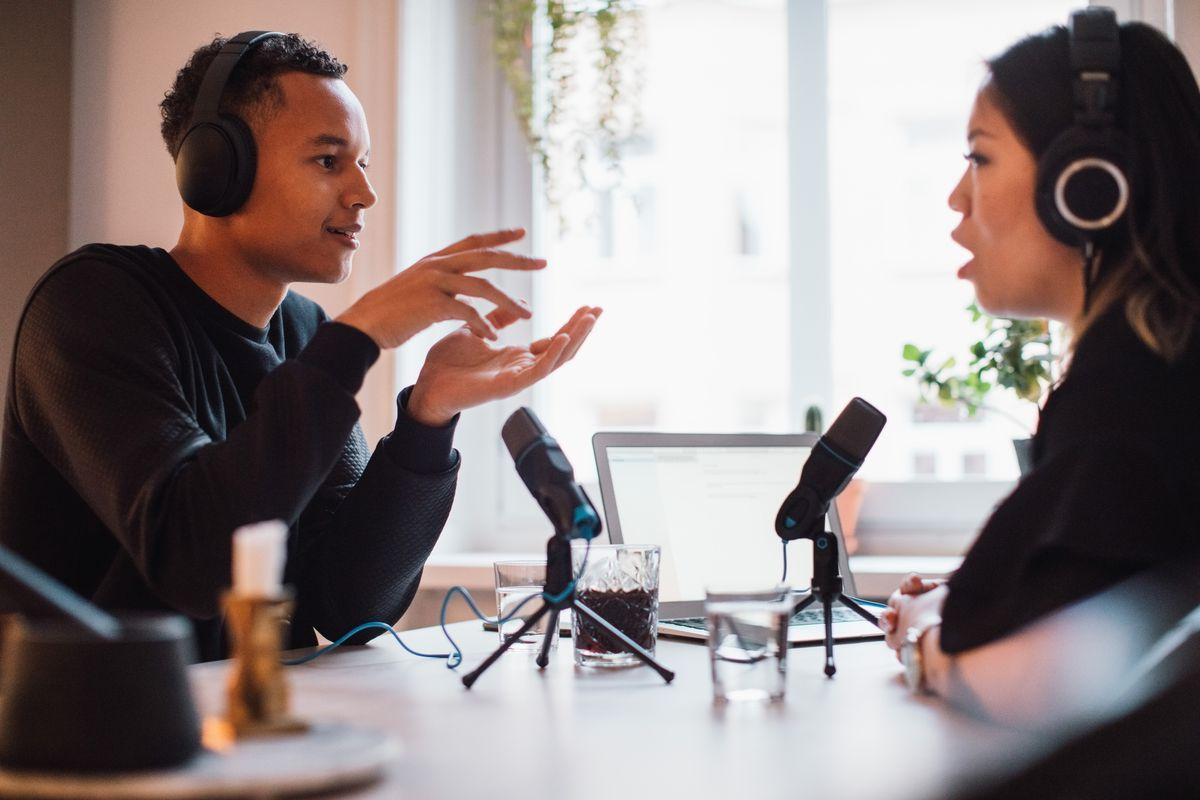Picture of two people speaking into microphones whille recording a podcast