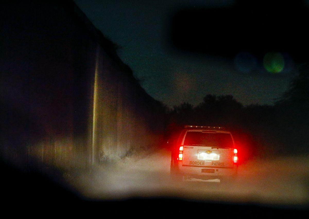 A Border Patrol agent drives along the border wall near McAllen, Texas, on Tuesday, June 22, 2021.