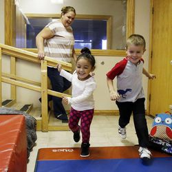Scarlett, left, and Eli play during the Autism Bridges preschool at Kids on the Move in Orem, Tuesday, Oct. 15, 2013. Eli is a typical peer model. In the background is tutor Sarah Winkelkotter.
