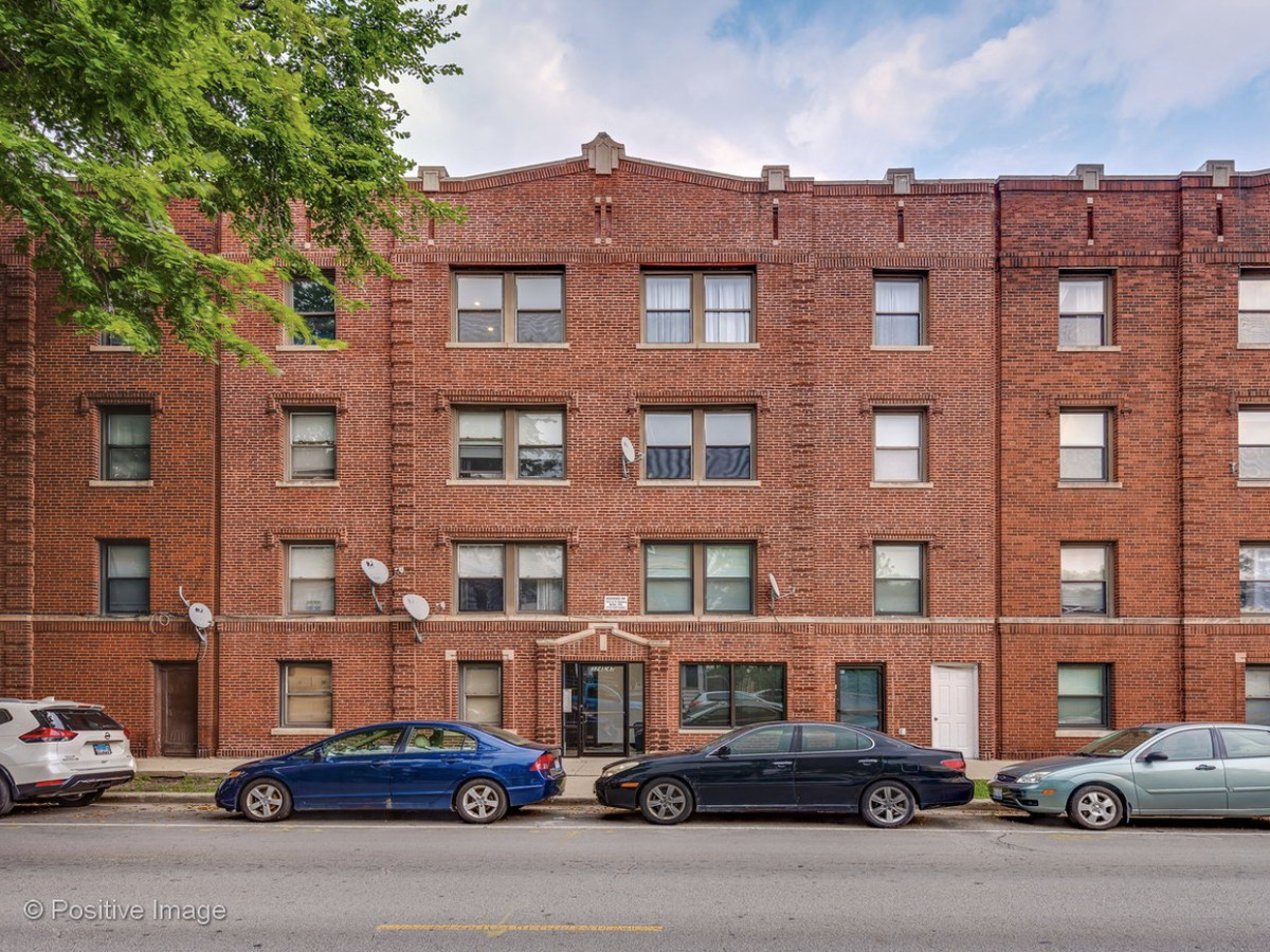 A mid-size brick building with cars parked outfront.