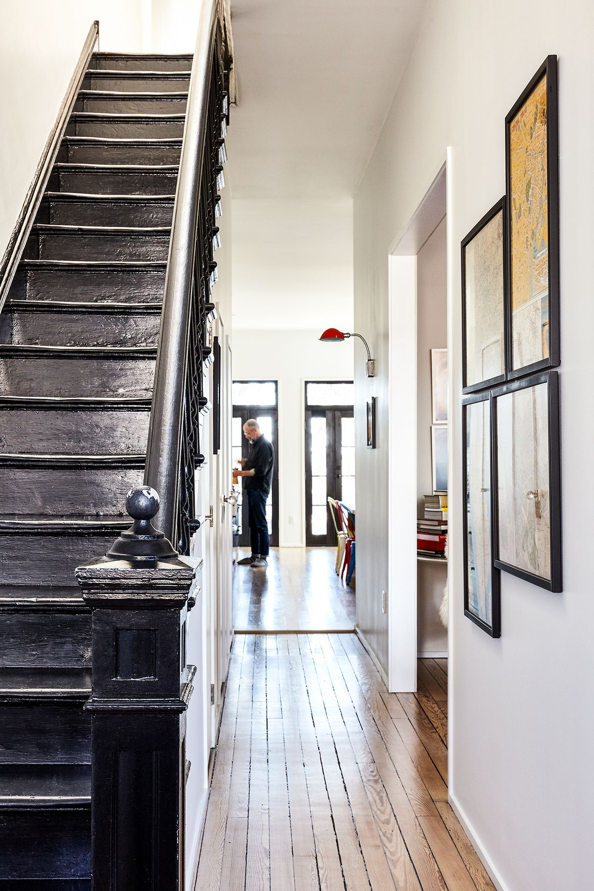 A hallway with a hardwood floor. There is a black staircase and bannister. There are multiple framed works of art on the white wall across from the staircase.