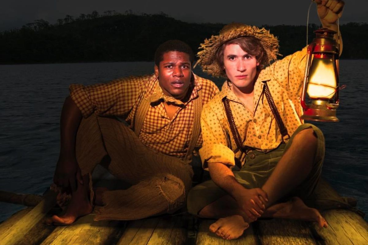 """Riding the raft down the MIssissippi is Conlon Bonner as Jim and Andrew Robertson as Huck Finn in Hale Center Theater Orem's production of """"Big River."""""""
