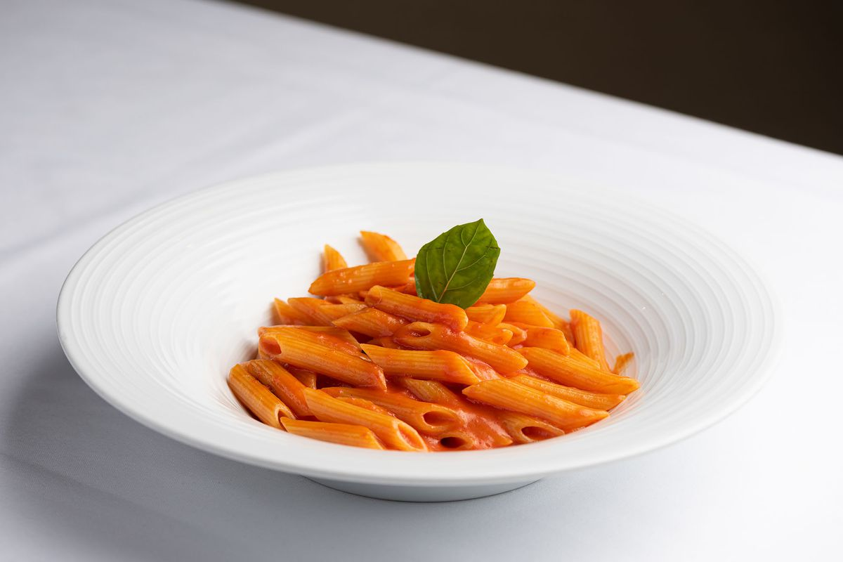 A plate of pasta with a single sprig of basil in a white bowl.