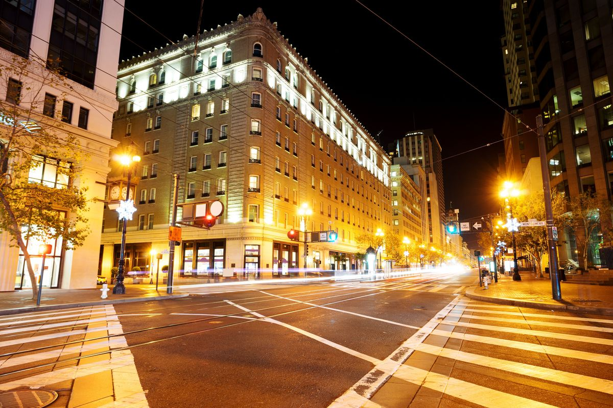 A downtown San Francisco intersection at night.