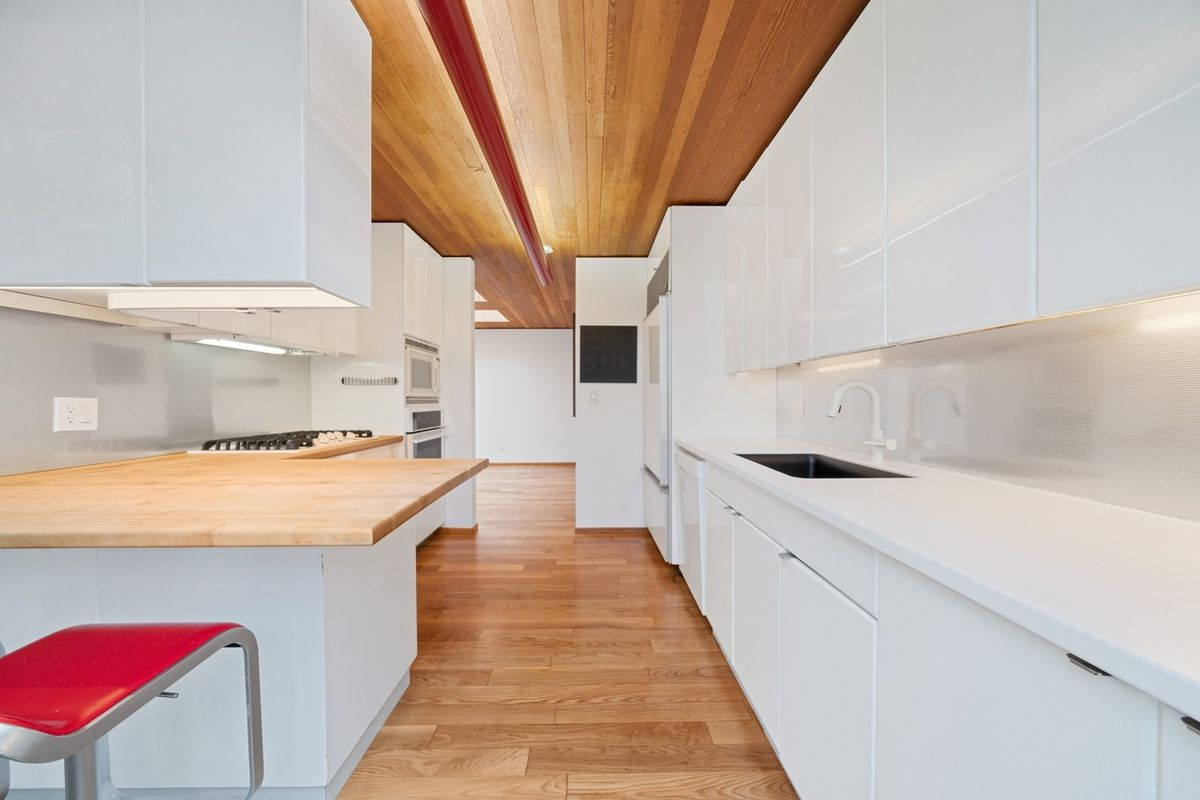 A white on white kitchen with white and wood counters and red stools. The floor and ceiling are wood and a linear light hangs from the ceiling.