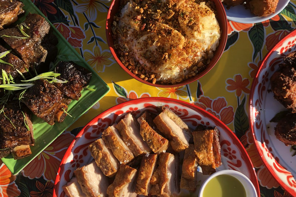 A floral, yellow-and-pink table is plated with crispy pork belly, oma's rice, and pork shoulder at Oma's Takeaway