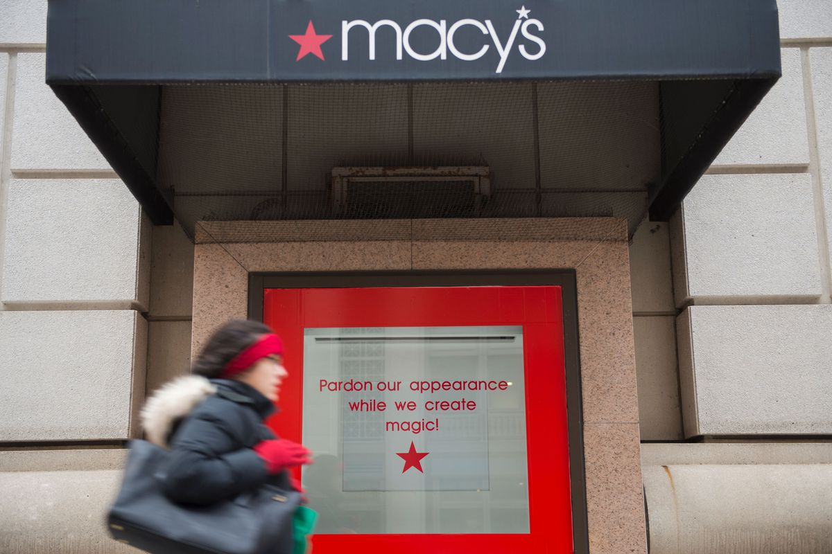 """A woman walks past a Macy's department store on January 5, 2017, in Washington, DC. The closed door reads """"Pardon our appearance while we create magic!"""""""