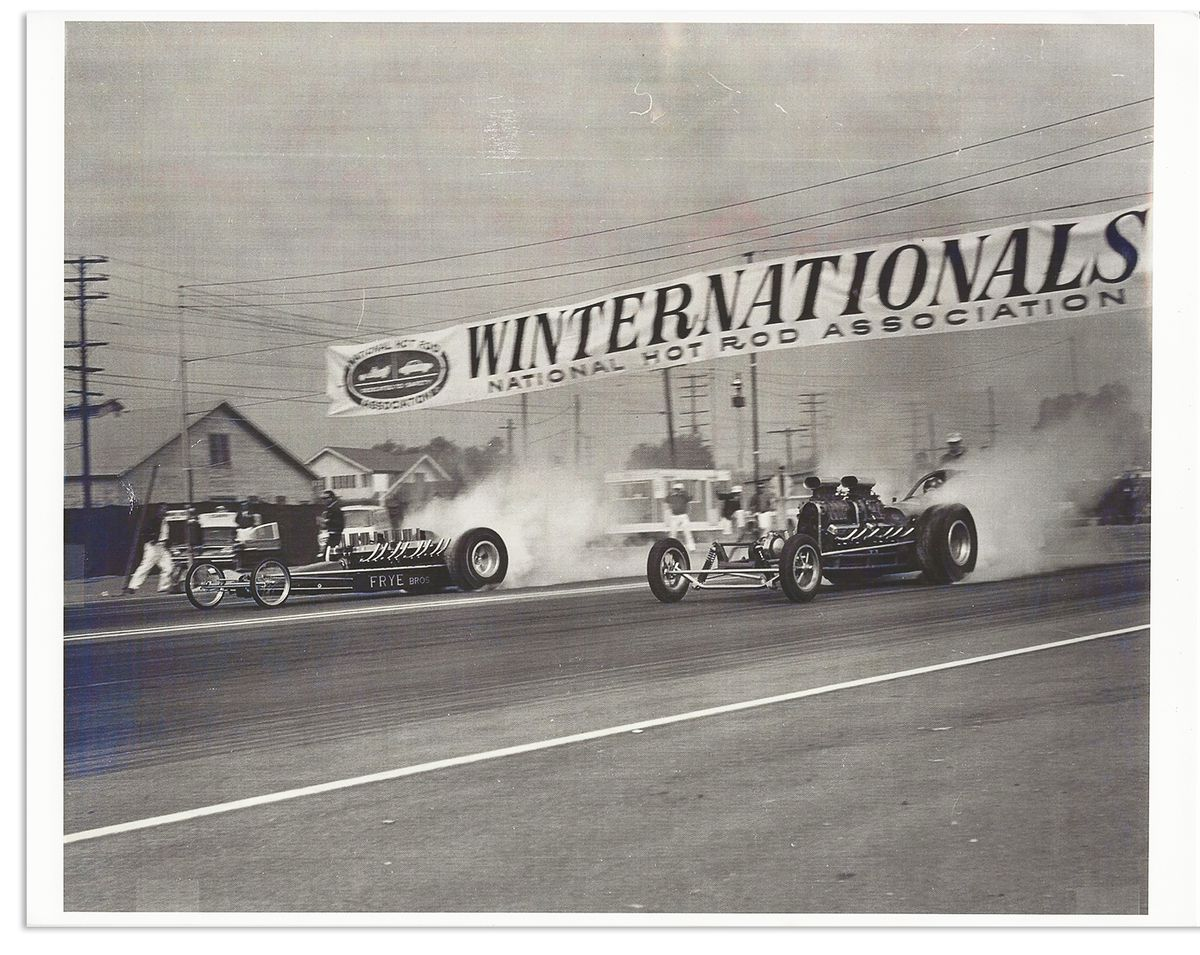 Photo at the start line of the 1983 Winternationals. Both cars have just begin, smoke streaming from their back tires. The Freight Train is in the far lane.