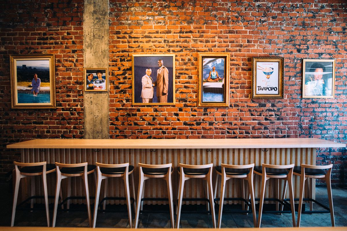 A long bar railing for indoor dining with brick and light wood.