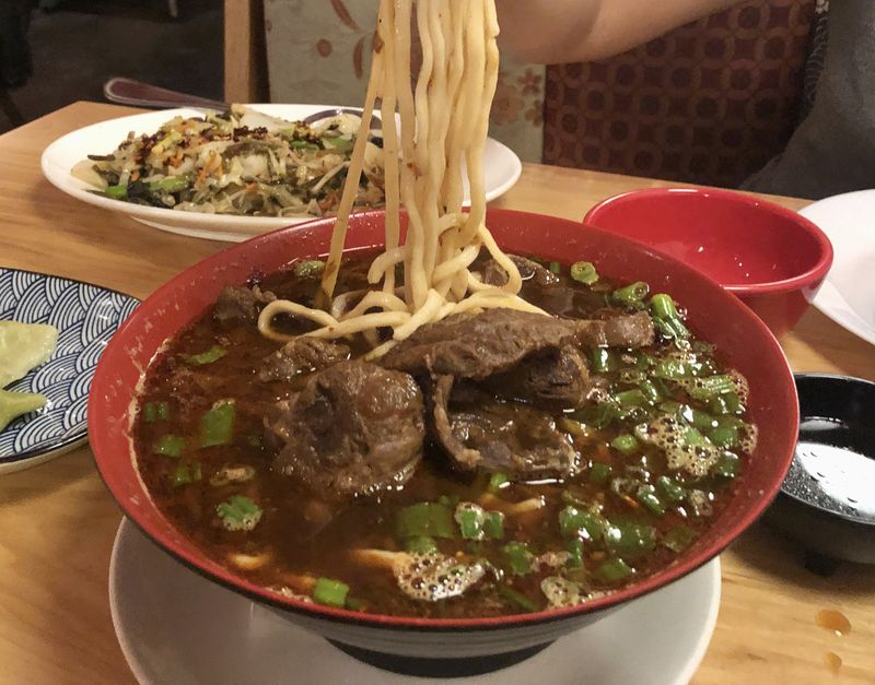 A bowl with soup, beef, and noodles.