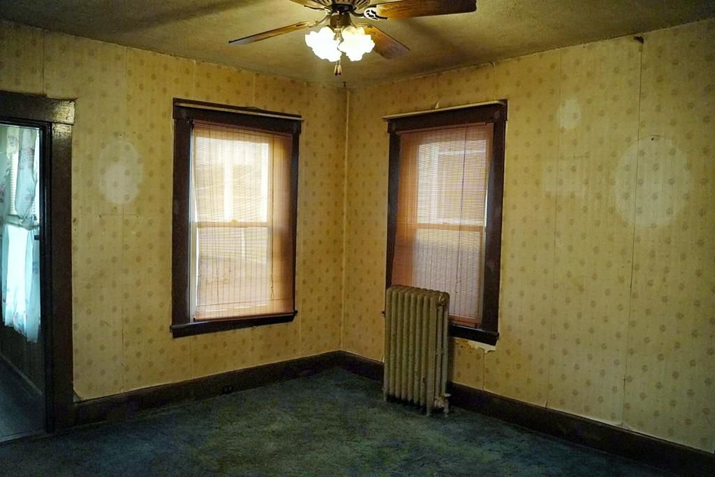 An empty room with a radiator and a ceiling fan.