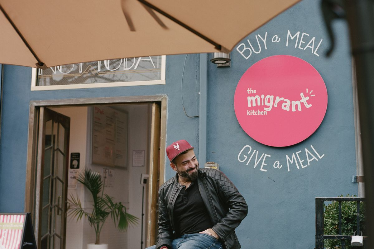 """A person wearing a red hat sits on a stool in front of a restaurant. A pink sign on the building reads: """"Buy a meal. Give a meal. The Migrant Kitchen."""""""
