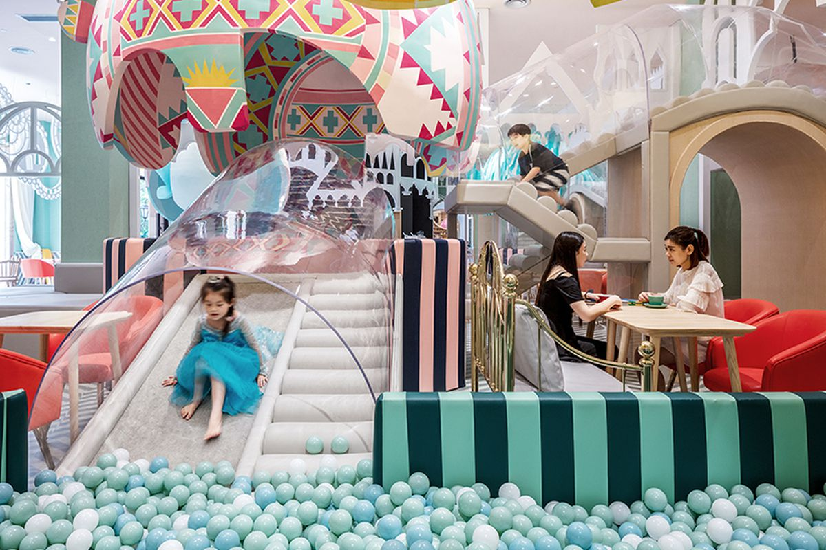 Interior photo of cafe-cum-playground with slide going into a ball pit, large balloon-like structures hanging from the ceiling, and cafe seating, all done up with bright colors, shapes, and patterns.