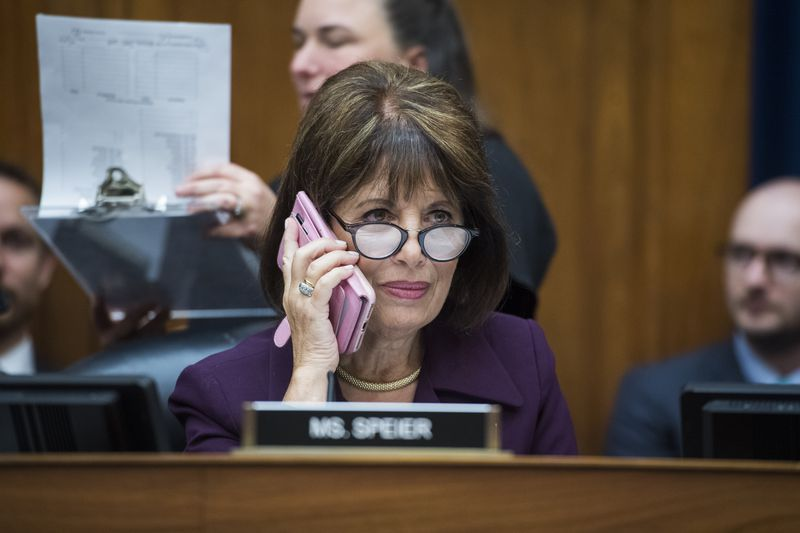 Speier on the House Intelligence Committee dais, talking on the phone.
