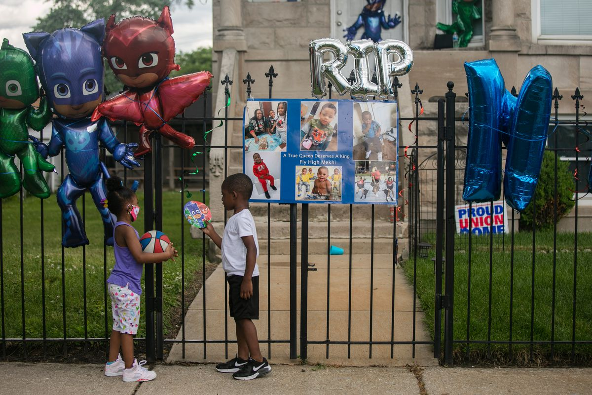 Kids play last June outside the Austin home of 3-year-old Mekhi James, who was shot and killed while his father was driving him home on Father's Day weekend.