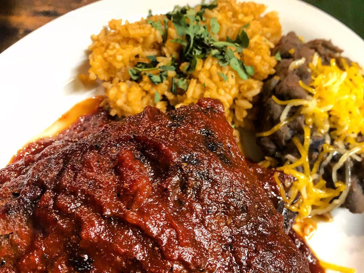 A close-up on saucy ribs with rice and a cheesy side dish blurred on the plate in the background