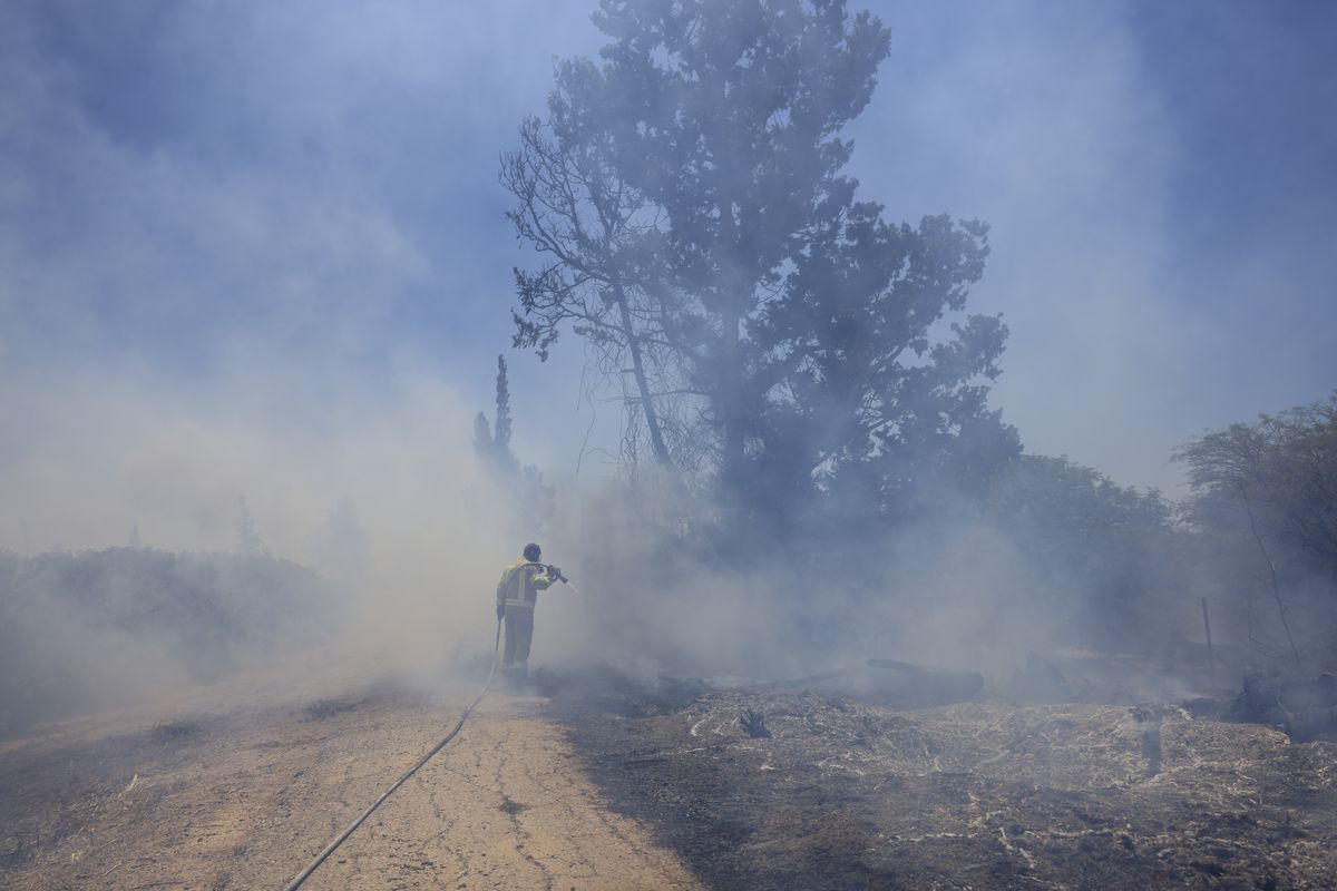 An Israeli firefighter attempts to extinguish a fire caused by an incendiary balloon launched by Palestinians from the Gaza Strip, on the Israel-Gaza border, Israel, Tuesday, June 15, 2021.
