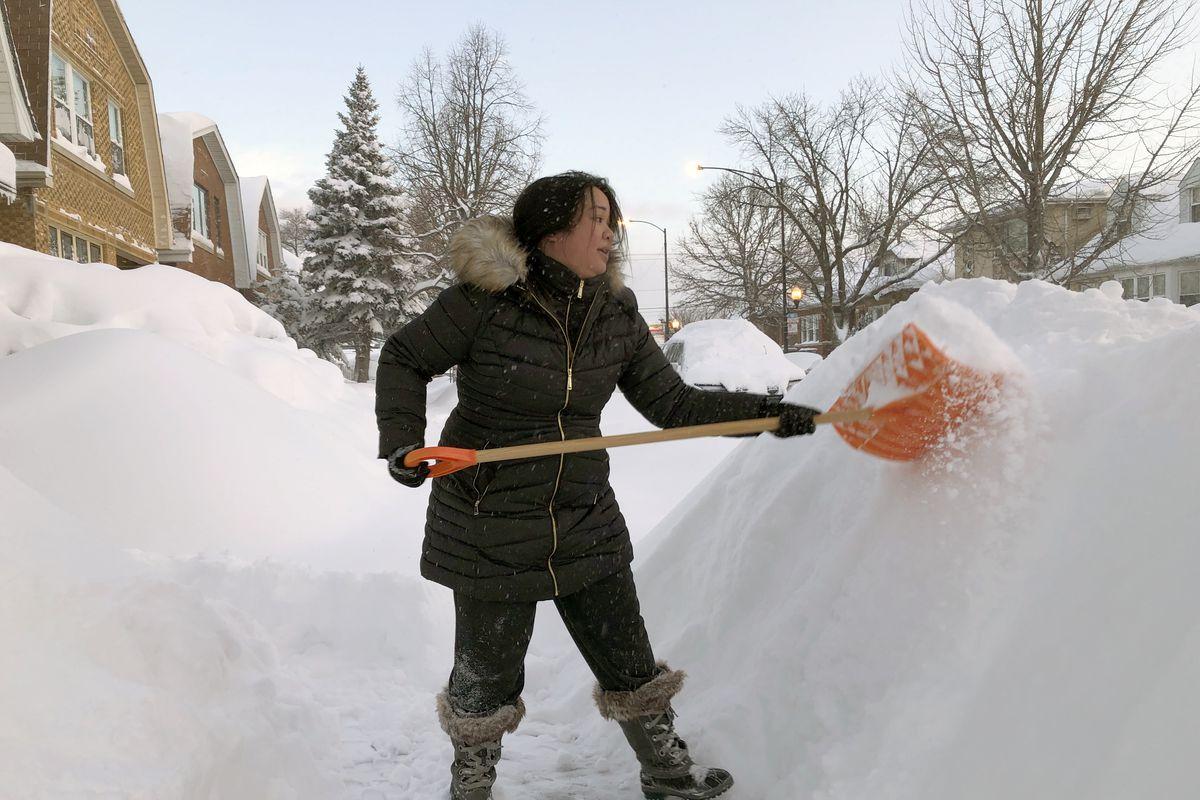 Melanie Maeda shovels her walkway Tuesday morning in Portage Park.