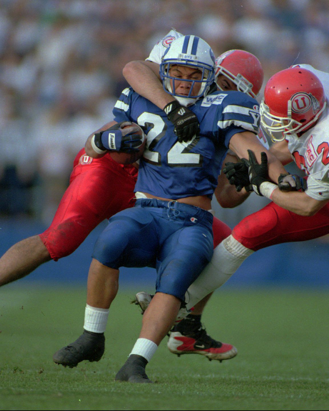 BYU runner Mark Atuaia is stacked up by Utha defenders Chad Kauhaahaa (behind) and Jeff Kirkman. PHOTO BY GARY MCKELLAR. (Submission date: 10/21/2002)