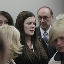 Alexis Somers, center, huddles with friends and family members at the conclusion of her father Martin MacNeill's murder trial in Provo's 4th District Court on Friday, Nov. 8, 2013