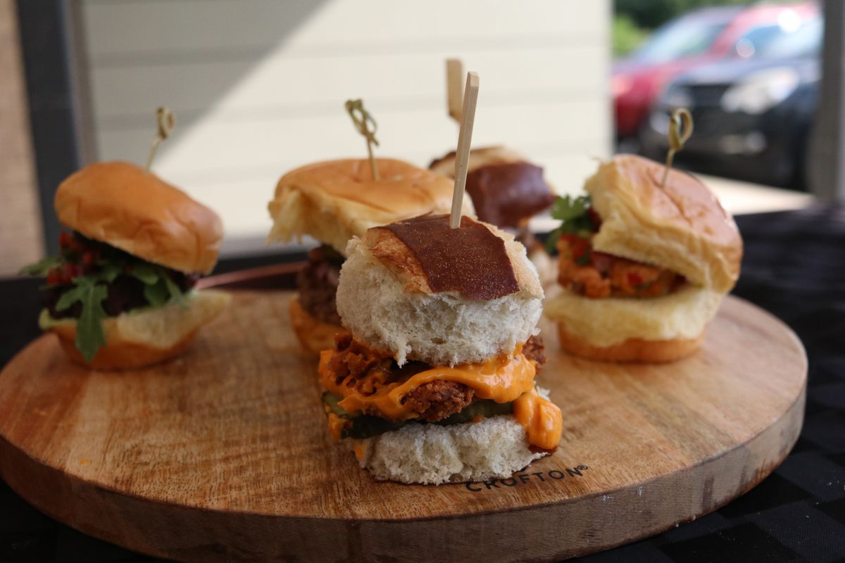 A bunch of sliders on a round wooden board.
