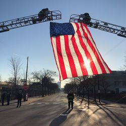 The Chicago Fire Department raises a flag outside the Cook County Medical Examiner's Office, Saturday, March 23, 2019, ahead of a procession for a 23-year-old off-duty officer who was fatally shot in River North.   Tyler LaRiviere/Sun-Times