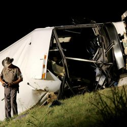 FILE - In this Aug. 8, 2008 photo, A Texas state trooper makes photographs at a bus accident scene on U.S. 75 North bound that killed several people in Sherman, Texas. Months after their state-certified vehicle inspection station was cited by federal authorities for failing to notice defects in a bus that crashed in North Texas, killing 17 passengers, brothers Alam and Cesar Hernandez shuttered their firm. But that didn't mean they were out of the vehicle inspection business.