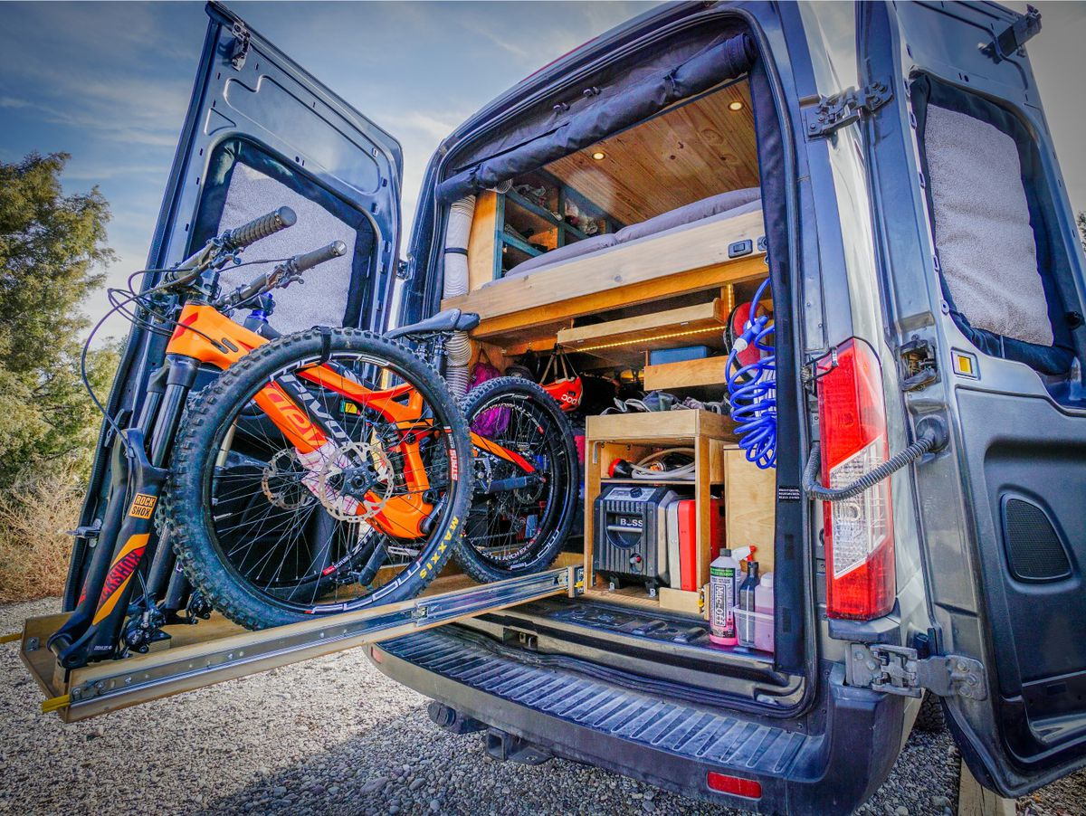 A camper van holds mountain bikes in a garage.