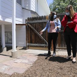 AJ Perez, Youth Services Youth Council co-chairwoman, shows Salt Lake County Mayor Jenny Wilson bricks with names of those who have impacted a new Division of Youth Services' Milestone Program house, including Mayor Wilson, in the backyard of the house in Sandy on Wednesday, July 8, 2020. The four-bedroom house was remodeled in partnership with Good Shepherd Lutheran Church and will help provide housing to young adults, ages 18-21, who are experiencing homelessness.
