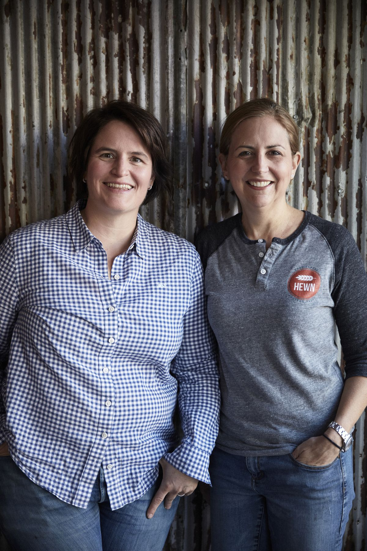 Two women smiling while wearing denim jeans.