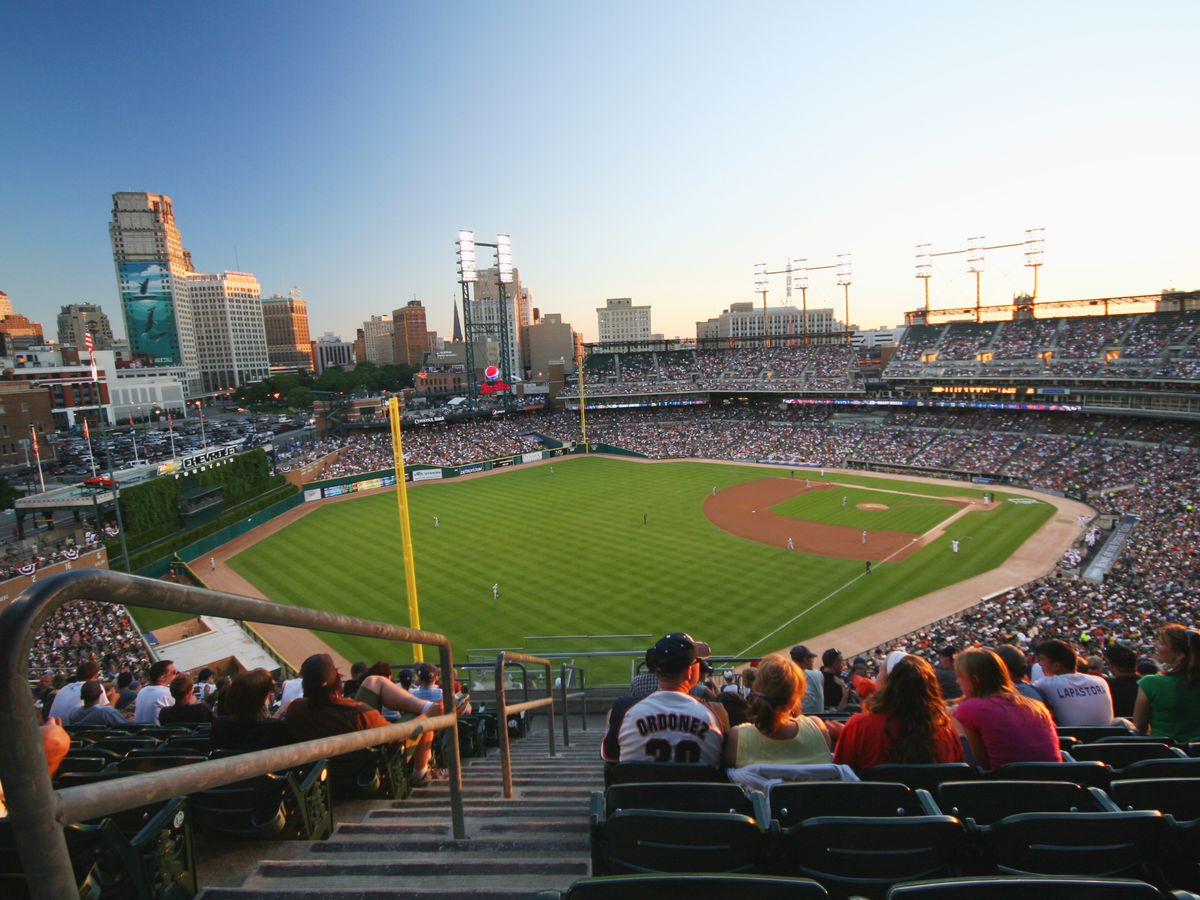 View of a baseball park from a seat in the upper stands. Many of the seats are filled with fans, though there are no players on the field. It's nearing sunset in the city.