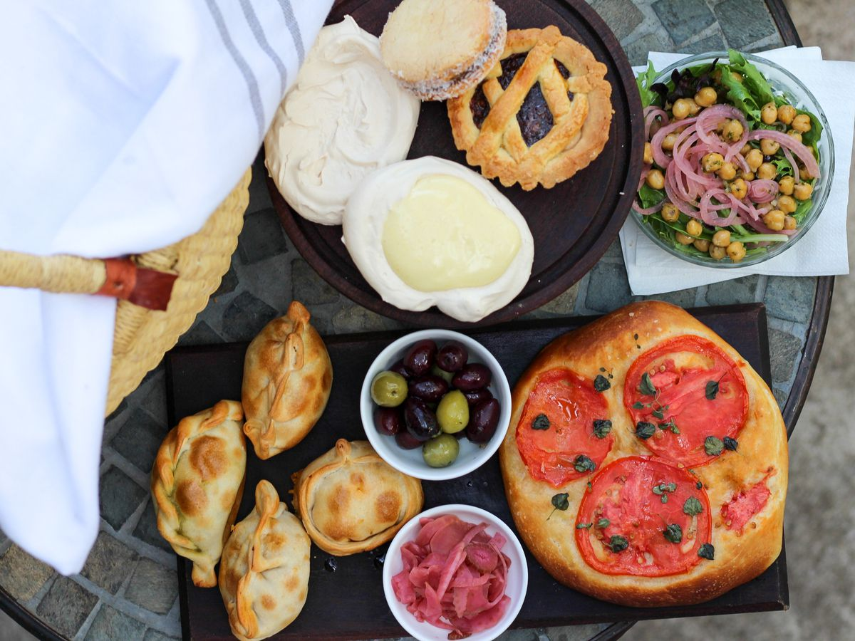 picnic basket with white cloth next to pastries and salads