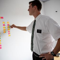 """Elder Tanner McKee, a missionary for The Church of Jesus Christ of Latter-day Saints, looks at sticky-notes tracking the progress of """"investigators,"""" those considering joining the church, on the wall of the home he shares with three other missionaries in Paranaguá, Brazil, on Saturday, June 1, 2019."""