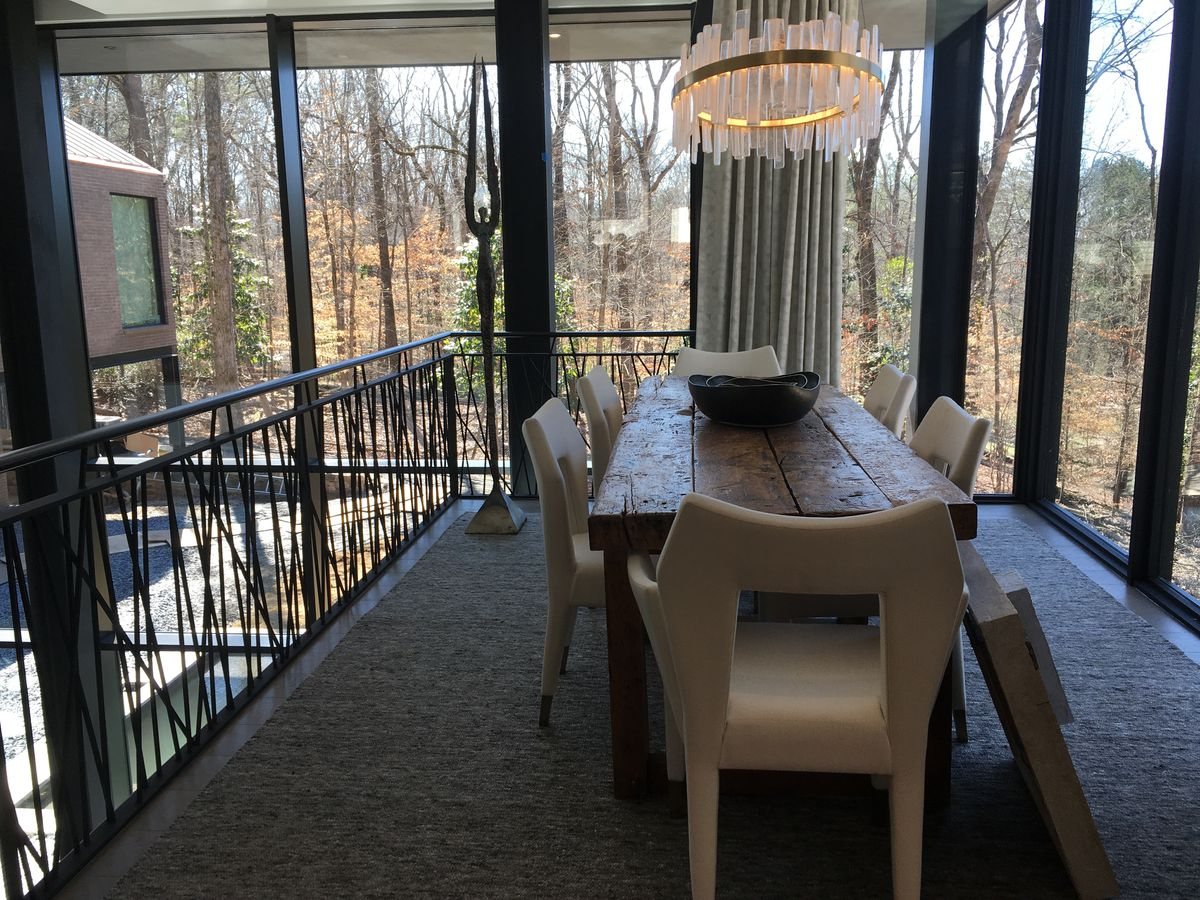 A big dining room with windows all around and woods beyond.