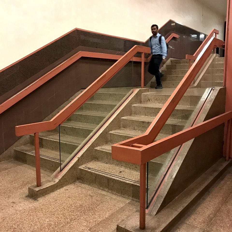 A staircase with terrazzo steps and a light red railing.