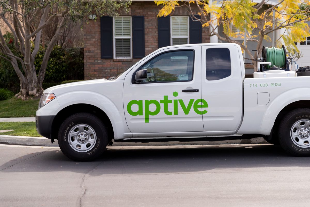 A white Aptive pick-up truck parked in front of a red brick home with pest control tools in the bed of the truck.