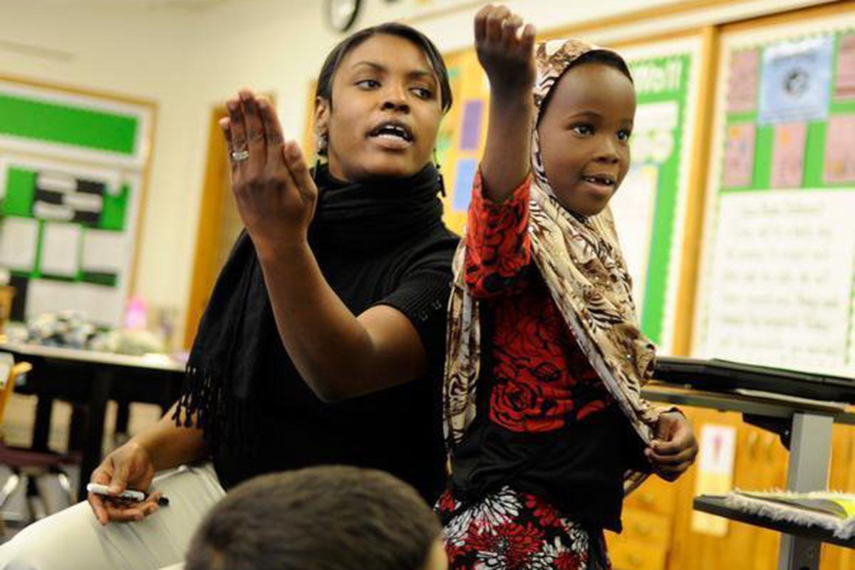 McMeen Elementary teacher JaMese Stepanek reads poetry with first-grader Citi Hejab.