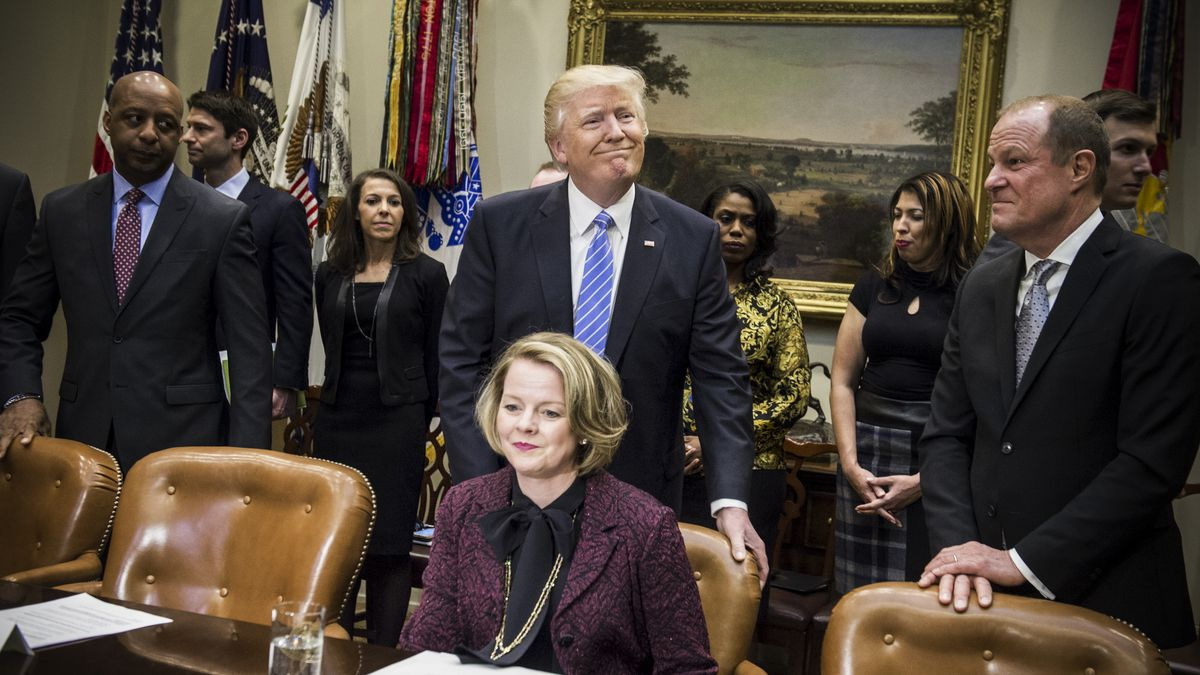 President Trump pushes in the chair for Jill Soltau, then-CEO of JOANN stores, alongside Art Peck, CEO of Gap Inc, and Marvin Ellison, then-CEO of JCPenney, during a meeting with retail industry leaders on February 15, 2017.