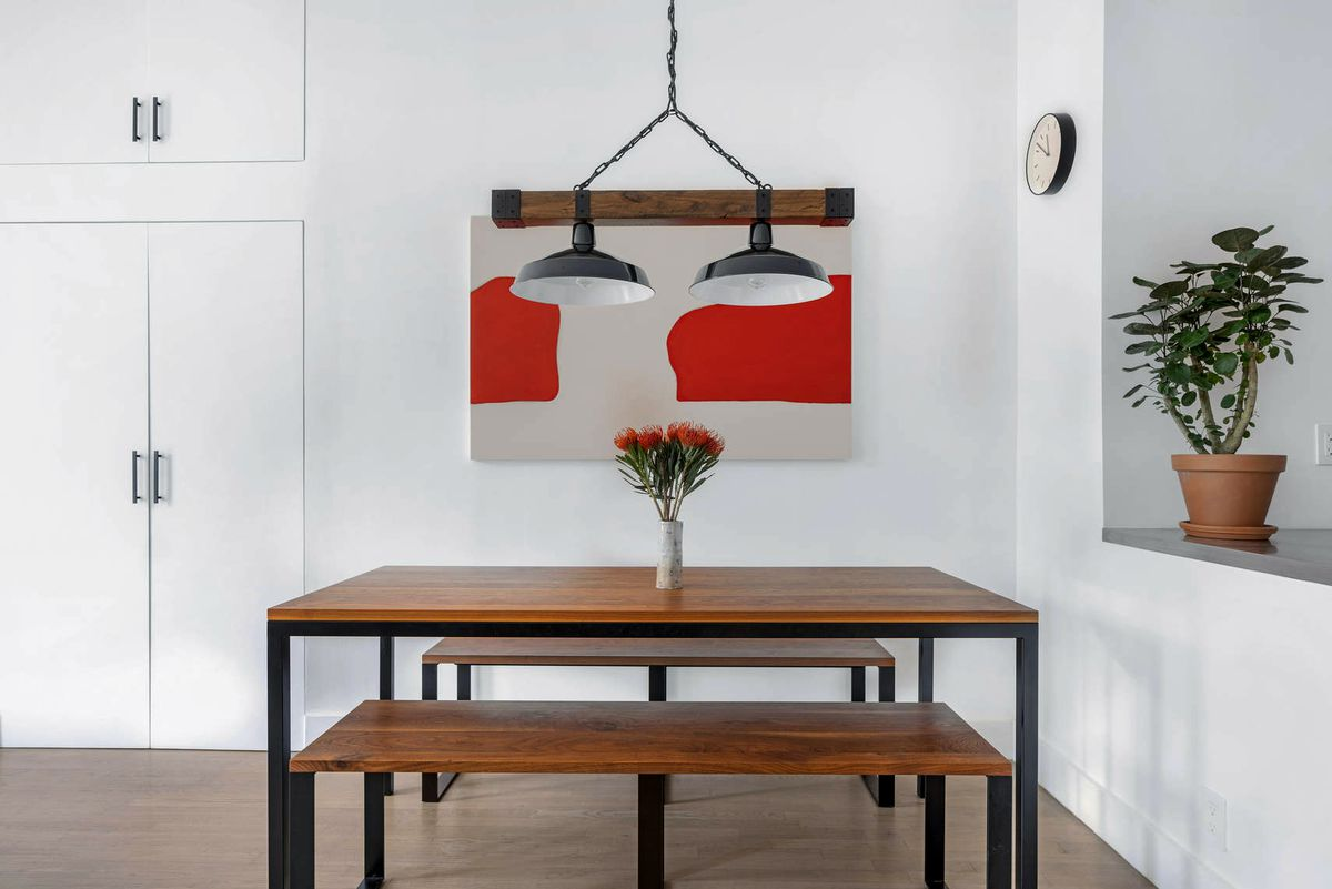 A dining area with a wooden table, hardwood floors, a hanging lamp, and white walls.