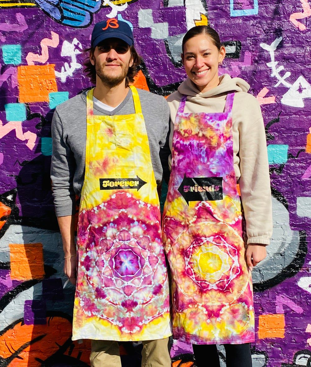 """Two people in colorful tie-dye aprons. The one on the left reads """"forever"""" with an arrow pointing right. The right reds """"friends"""" with an arrow pointing left."""